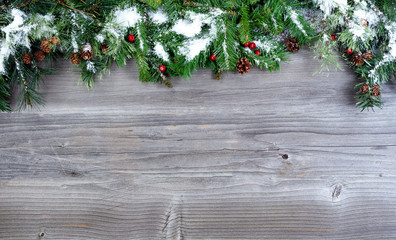 Top Border of Snowy Christmas tree evergreen branches on a rustic wooden background