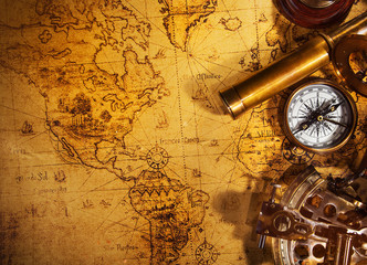 Old vintage navigation equipment on old world map.