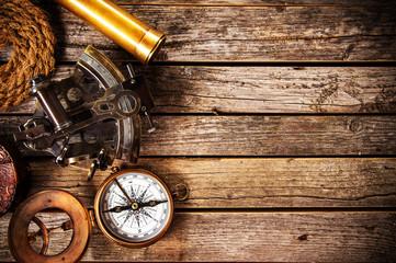 Old vintage navigation equipment on old wooden background.