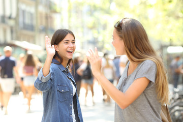 Friends meeting and greeting in the street