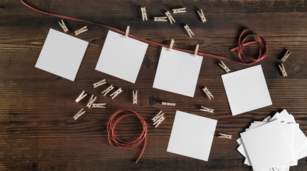 Blank frames of photo, rope and clothespins on wood background. Flat lay.