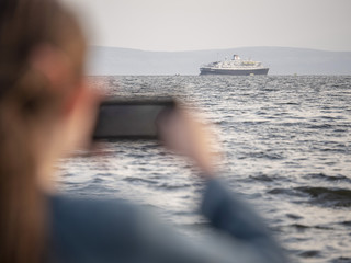 Cruise ship in the ocean, in focus, young girl taking picture on her phone out of focus.