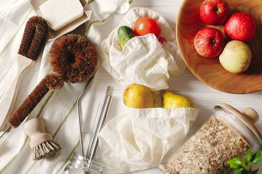 sustainable lifestyle concept. zero waste. eco natural coconut soap and brushes for washing dishes, metal straws, granola in glass, eco bags with fruits, flat lay. plastic free items.