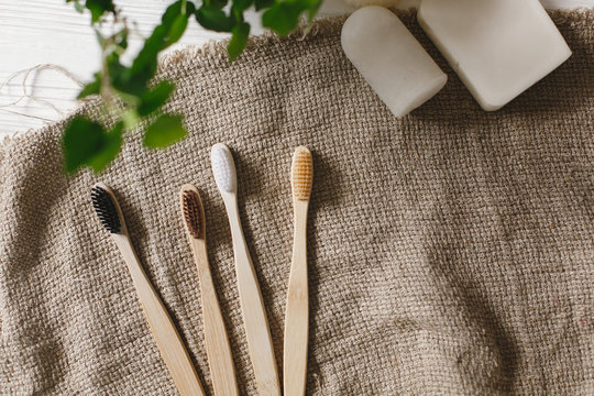 eco natural bamboo toothbrushes on rustic background with greenery. sustainable lifestyle concept. zero waste flat lay. bathroom essentials, plastic free items