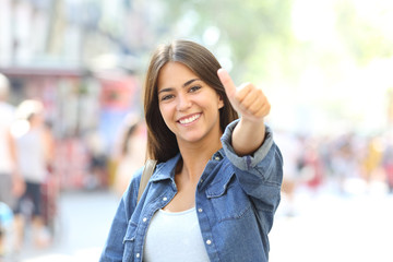 Happy girl posing with thumb up in the street