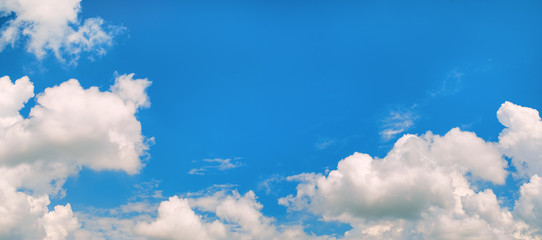 Blue sky background with cumulus clouds. Panoramic shot.