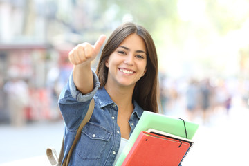 Happy student posing with thumbs up in the street