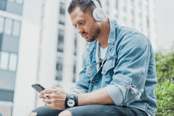 Close up of young man in earphones and looking at mobile phone.