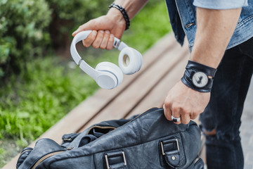 Close up of man putting headphones in his black sports bag