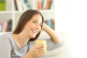Happy woman thinking looking at side at home