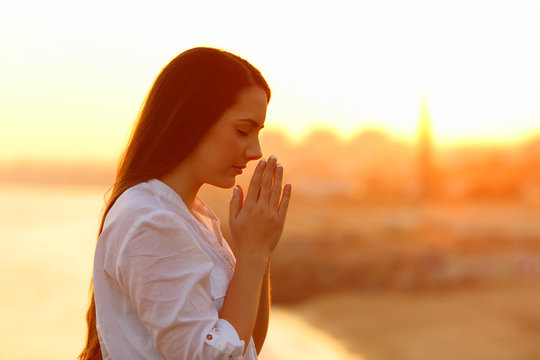 Profile of a concentrated woman praying at sunset