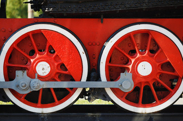Two old red steam locomotive wheels on rails closeup.