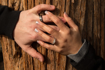Engaged couple with her hand on top of his on Juniper tree