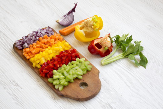 Chopped fresh vegetables (carrot, celery, onion, colored peppers) arranged on cutting board on white wooden surface, side view.