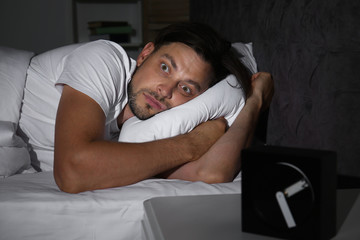 Man suffering from insomnia in bed at home