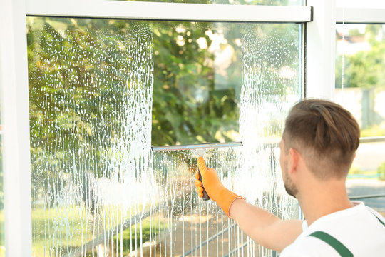 Male janitor cleaning window with squeegee indoors