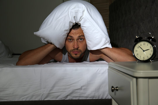 Man covering head with pillow in bed at home. Sleep disorder
