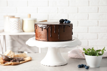 Fresh delicious homemade chocolate cake with berries on table against brick wall