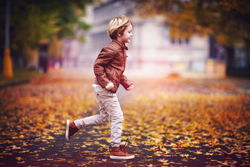 smiling young boy, kid having fun in autumn city park among fallen leaves