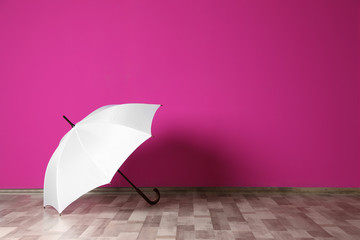 Wall Mural - Beautiful open umbrella on floor near color wall with space for design