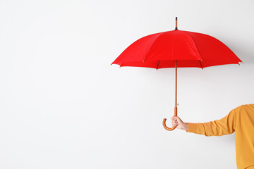 Wall Mural - Person holding open umbrella on white background with space for design