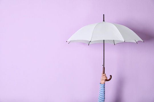 Person holding bright open umbrella on color background with space for design