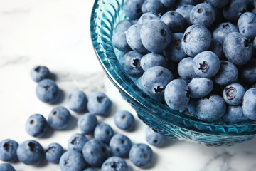 Bowl with fresh blueberries on marble table, closeup