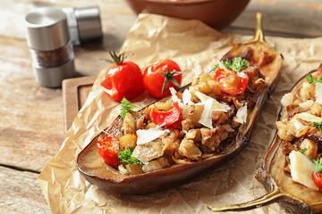 Tasty stuffed eggplants on wooden table, closeup