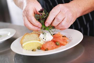 chef plating smoked salmon appetizer