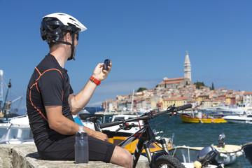 Kroatien, Istrien, Rovinj, Hafen, Mountainbiker bei Pause blickt auf sein GPS-Gerät