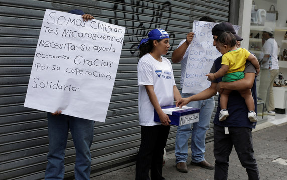 A man gives cash to Nicaraguan refugees asking for money to help tide them over after fleeing their country due to unrest, along a street in San Jose