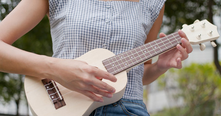 Woman play ukulele at outdoor