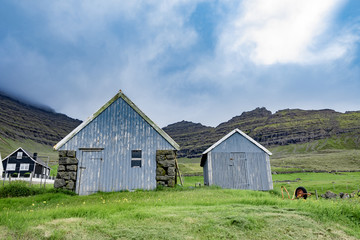 Beautiful view of blue faded wooden barn with green grass of sheeps farm and high mountain cliff in the background with cloudy weather sky in Faroe Islands rural