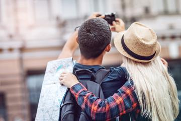 Back view of stylish traveling couple using photo camera and taking photos of city