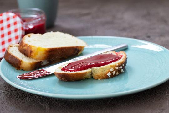 Eine Scheibe Hefezopf mit Marmelade bestrichen