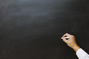 young teen hand to draw and writing something on blackboard with chalk. Education back to school concept / chalkboard.  Leave blank empty space to write text.