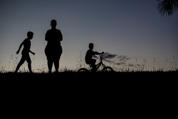 Silhouette of a boy walking, another boy on a bicycle and a woman - outdoors
