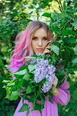 Beautiful girl with colorful dyed hair and perfect makeup standig next to lilac bush