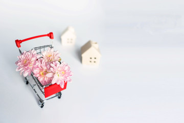 A red shopping cart fulls with pink flowers, two white small houses behind it, on white background with copy space on right. Shopping, home decorating and gardening concept.