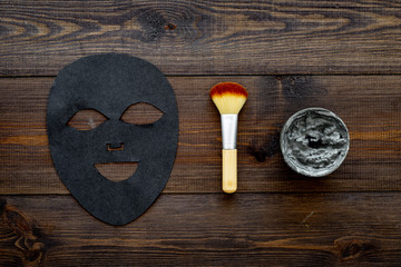 Black facial mask. Black head remover mask. Mask with clay on dark wooden background top view copy space