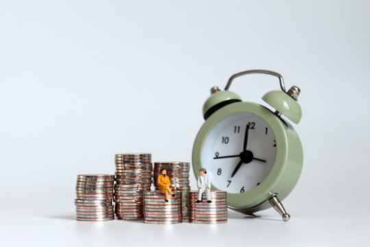 A preparatory concept for post-retirement cost of living. Miniature men and women sitting on a pile of coins with alarm clocks.