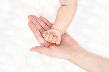 赤ちゃんの小さな手を包むお母さんの大きな片手のアップ。成長と健康を喜ぶ母。母性、愛情、幸せ、育児、健康のイメージ