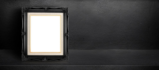 Blank black vintage frame leaning at black interior cement room background,banner mock up template for display of design,leave side space for adding text for advertising