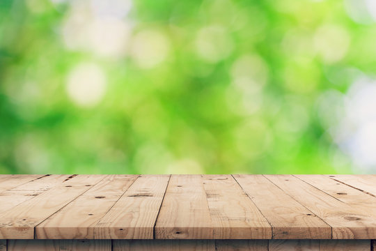Empty wooden table top and green bokeh display montage for product with space.