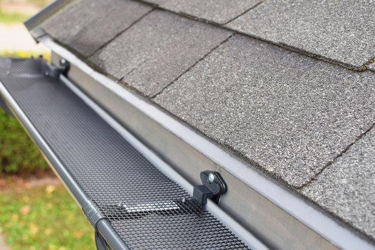 Plastic guard over new dark grey plastic rain gutter on asphalt shingles roof at shallow depth of field.