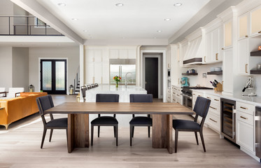 Beautiful dining room and kitchen in new luxury home with partial view of living room and entry