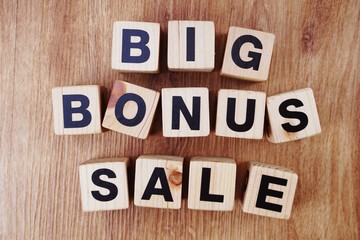 big bonus sale text alphabet letters on wooden background