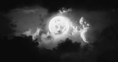 Artistic black and white panorama atmosphere image of beautiful bright moon and dark clouds on Halloween scary night scene.Image of moon furnished by NASA.