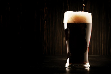Papiers peints Biere, Cidre Dark english beer, ale or stout is poured into glass, dark bar counter, space for text, selective focus