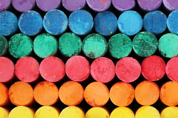 Chalk sticks multi color (purple,blue,green,red,orange,yellow) front view. High detail colorful dusky surface.